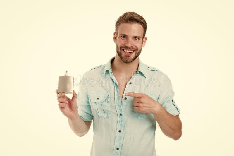 Glücklicher Mannpunktfinger an der Parfümflasche Bärtiges Mannlächeln mit dem desodorierenden Mittel lokalisiert auf weißem Hinte stockfotografie