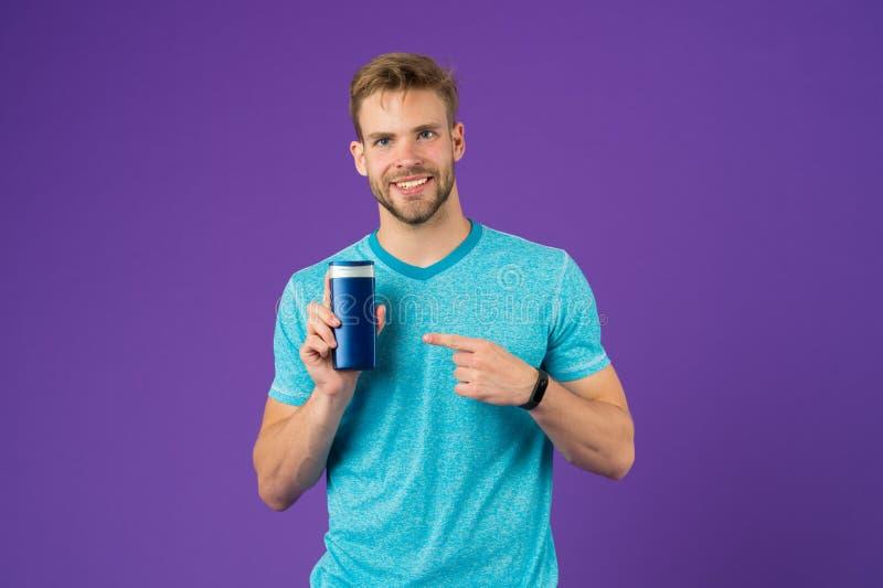 Glücklicher Mannpunktfinger am Gelrohr auf violettem Hintergrund Bärtiges Mannlächeln mit Shampooflasche Skincare und Haarpflege stockfoto