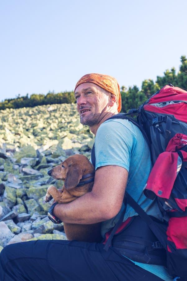 Glücklicher Mannreisender mit einem lustigen Hund lizenzfreie stockbilder