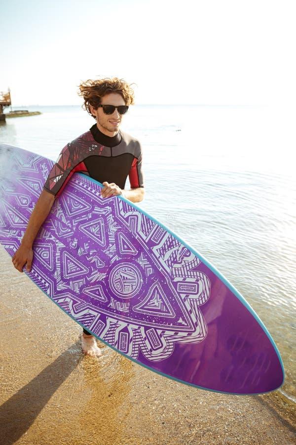 Glücklicher Mannsurfer mit dem surfenden Brett, das auf dem Strand läuft stockbild