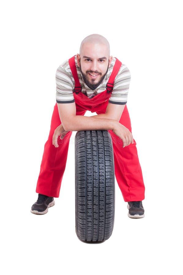 Glücklicher Mechaniker, der auf einem Neuwagenrad stillsteht stockfotos