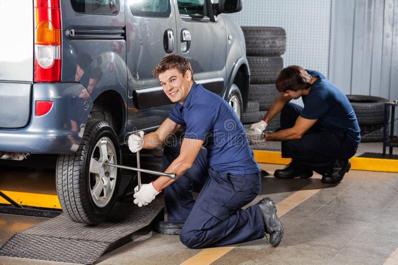 Glücklicher Mechaniker Fixing Car Tire an der Reparaturwerkstatt stockbild