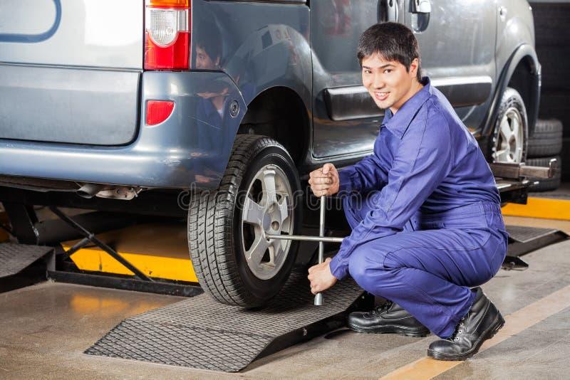 Glücklicher Mechaniker Fixing Car Tire mit Rim Wrench lizenzfreie stockfotografie