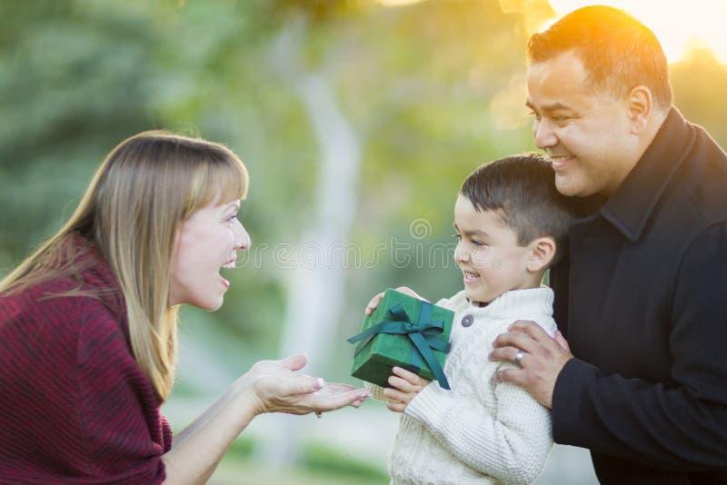 Glücklicher Mischrasse-Sohn, der seiner Mutter Geschenk übergibt stockbilder