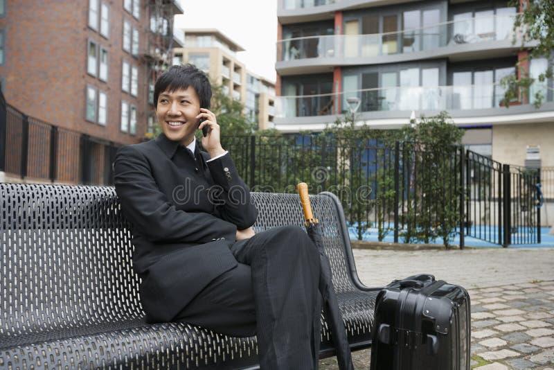 Glücklicher mittlerer erwachsener Geschäftsmann mit Gepäck unter Verwendung des Handys auf Bank lizenzfreie stockbilder