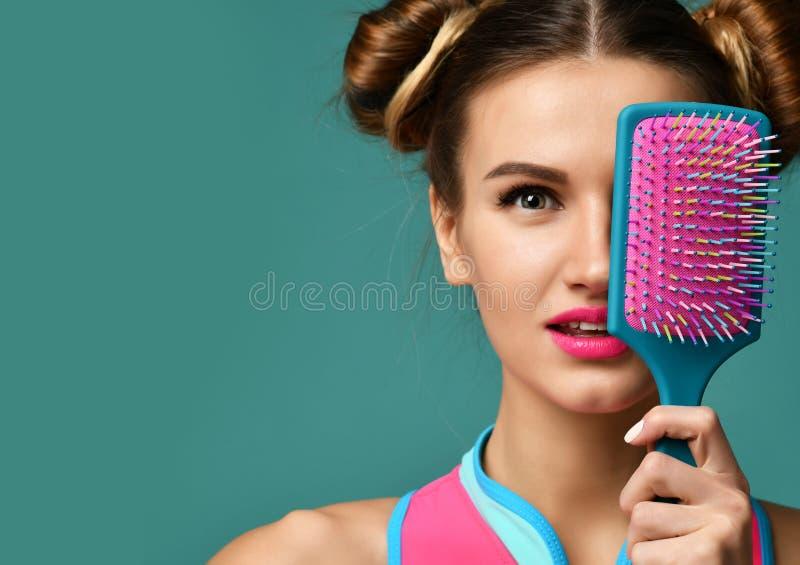 Glücklicher Mode Brunette-Frauenabschluß mustert mit bunter rosa blauer großer Haarkammbürste stockfotos