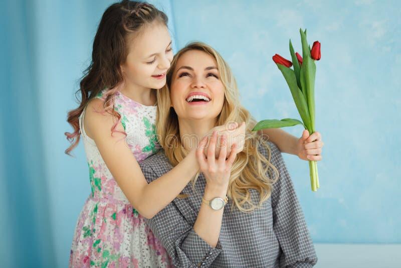 Glücklicher Mutter`s Tag Kindertochter beglückwünscht Mütter und gibt ihr eine Postkarte und blüht Tulpen lizenzfreies stockbild