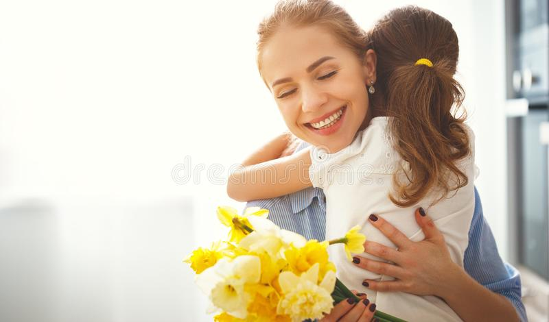 Glücklicher Mutter ` s Tag! Kindertochter gibt Mutter einen Blumenstrauß von f