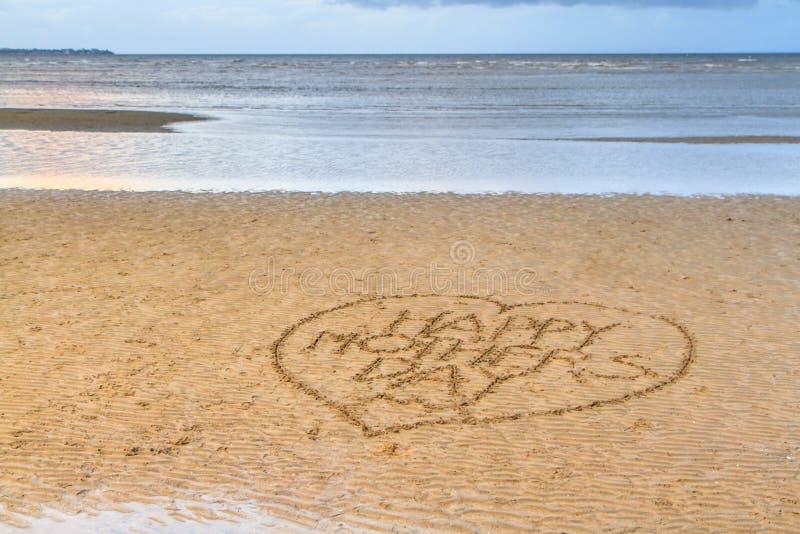Der glückliche Tag der Mutter geschrieben in den Sand stockfotos