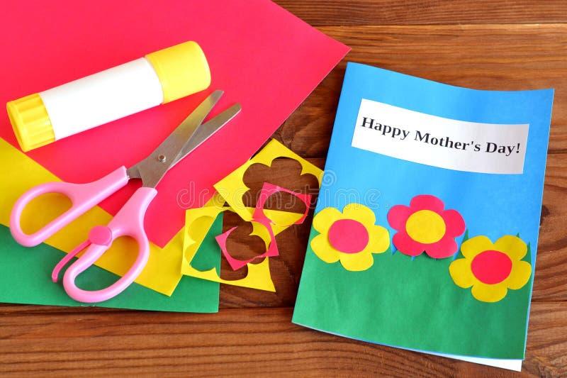 Glücklicher Muttertag der Grußkarte - Kinderhandwerk Scheren, Kleber, Papierschrotte, Papierblätter auf braunem hölzernem Hinterg stockbild