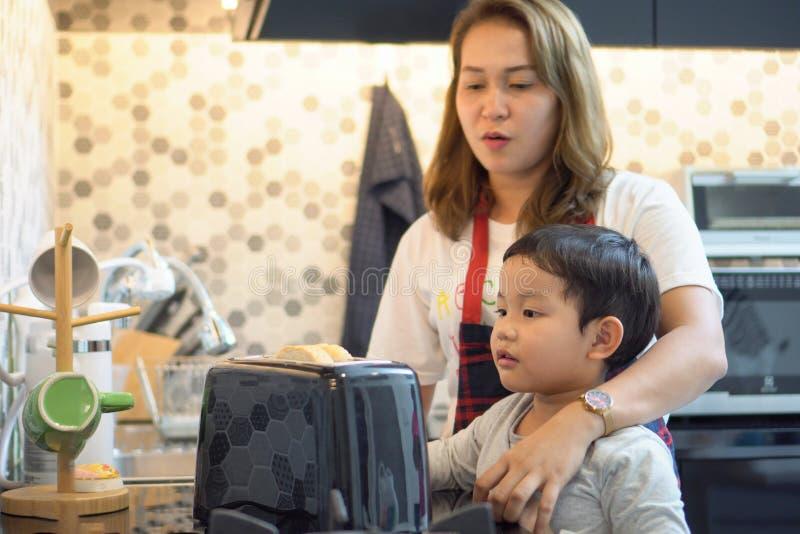glücklicher Mutterunterrichtssohn, der zu Hause Frühstückstoastbrot mit Küche des Toasters zusammen macht Liebevolle Familie Kind lizenzfreie stockfotos