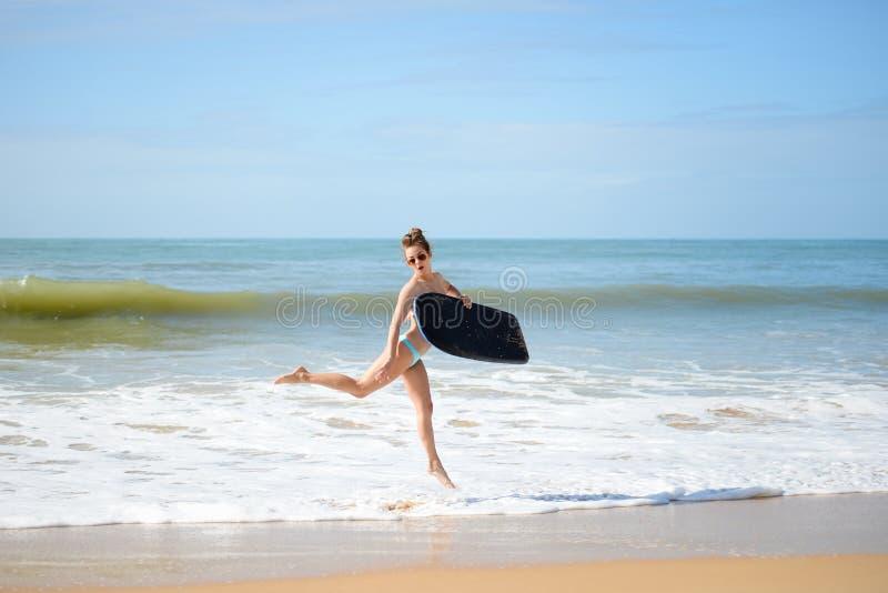 Glücklicher netter Betrieb des frohen Surfermädchens, der am Ozeanstrandwasser surft Weibliche Bikiniüberschrift für Wellen mit S stockfotos