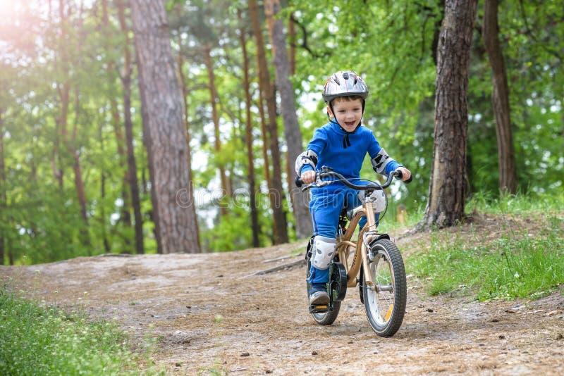 Glücklicher netter blonder Kinderjunge, der Spaß sein erstes Fahrrad am sonnigen Sommertag, draußen hat Kind, das Sport macht Akt stockbild