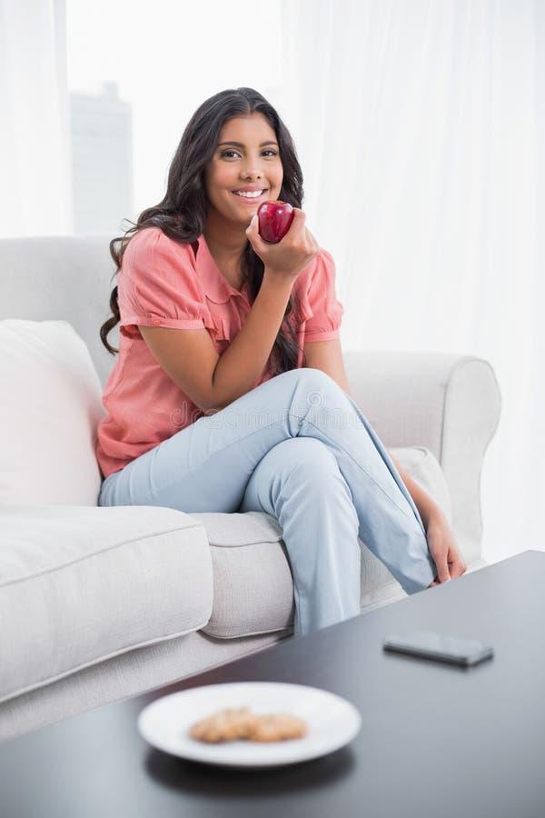 Glücklicher netter Brunette, der auf der Couch hält roten Apfel sitzt lizenzfreies stockfoto