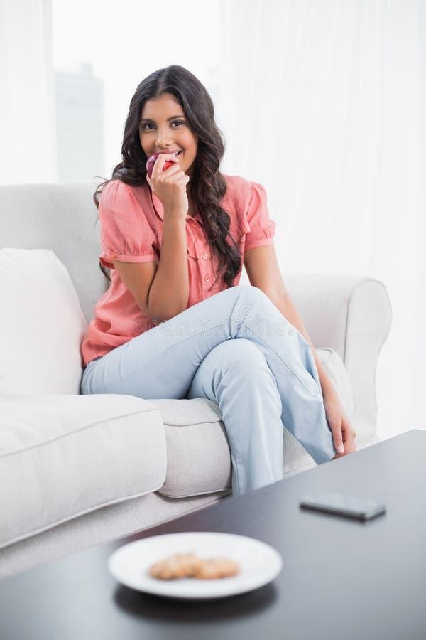 Glücklicher netter Brunette, der auf der Couch isst roten Apfel sitzt lizenzfreies stockfoto