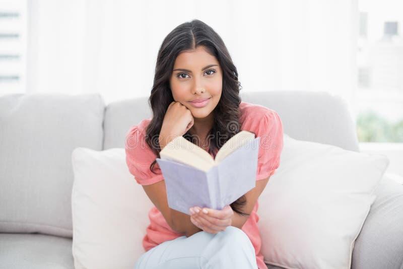 Glücklicher netter Brunette, der auf der Couch liest ein Buch sitzt stockfoto
