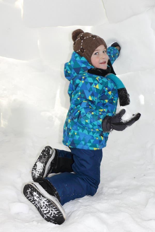 Glücklicher netter Junge mit einem Stück Schnee in seinen Händen, die einen Iglu sitzen stockfotografie