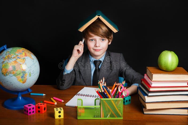 Glücklicher netter kluger Junge sitzt an einem Schreibtisch in Gläsern und in einem Lächeln Kind ist bereit, mit einer Tafel auf  lizenzfreies stockfoto