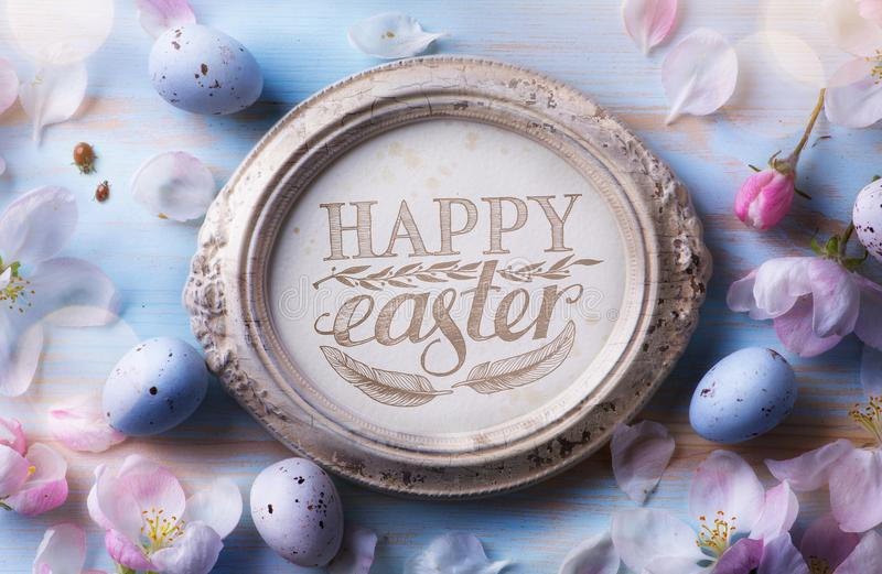 Glücklicher Ostern-Hintergrund; Osterei- und Frühlingsblumen auf blauem t lizenzfreie stockfotos