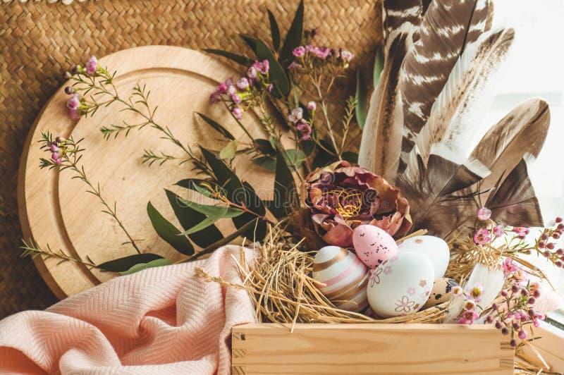 Glücklicher Ostern-Hintergrund _rosa easter Osterei in ein Nest mit Blumen- Dekoration und Feder nahe d Fenster lizenzfreie stockbilder