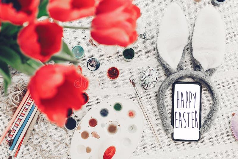 Glücklicher Ostern-Text auf Telefonschirm Jahreszeit ` s Grußkarte bunn stockfoto