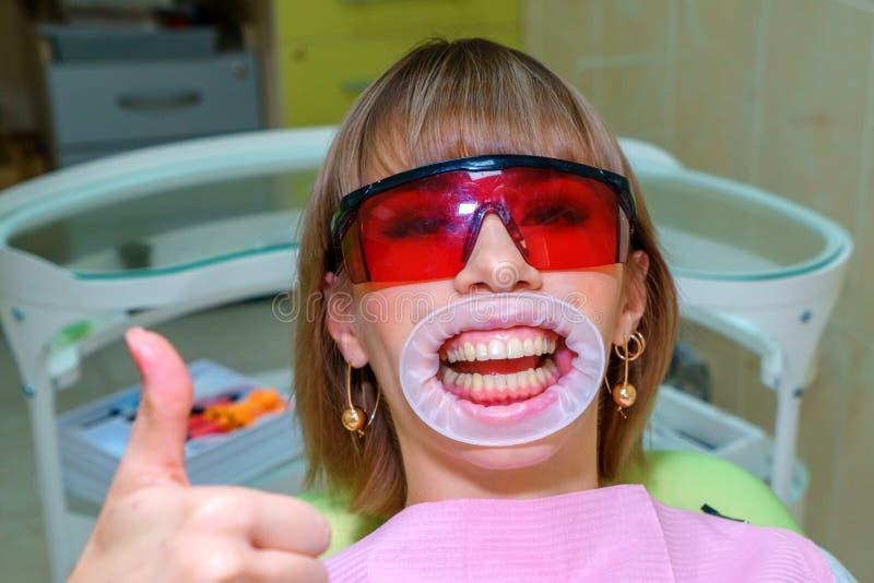 Glücklicher Patient der Zahnheilkunde im Stuhl in den Schutzbrillen stockbilder