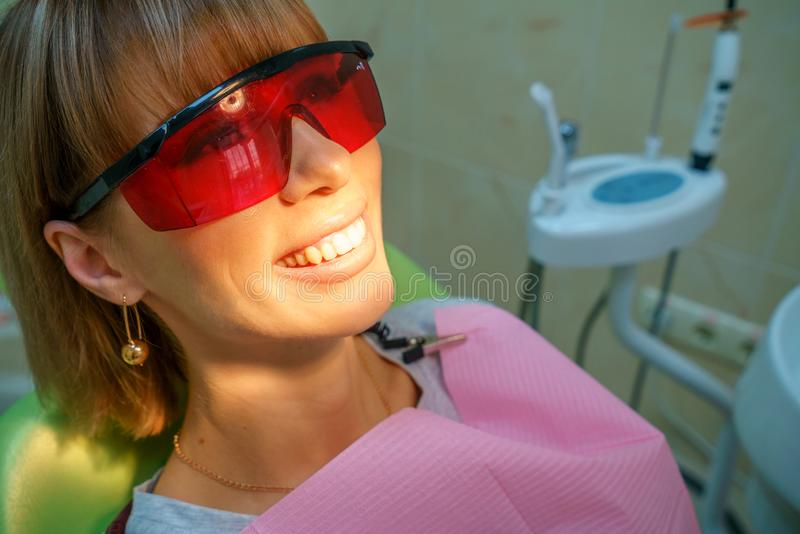 Glücklicher Patient der Zahnheilkunde im Stuhl in den Schutzbrillen lizenzfreies stockbild