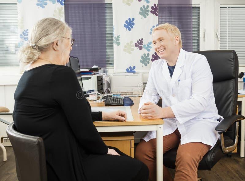 Glücklicher Patient Doktor-Communicating With Senior am Schreibtisch lizenzfreie stockfotografie