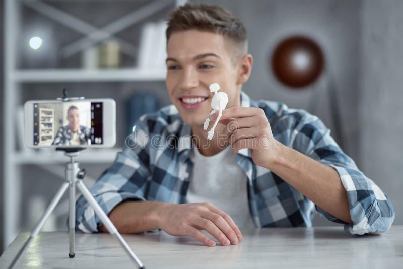 Glücklicher populärer Blogger, der zu Hause ein neues Video herstellt stockfotos