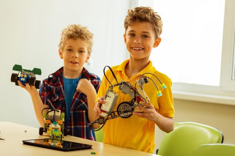 Glücklicher positiver intelligenter Junge, der seinen Roboter zeigt lizenzfreies stockfoto