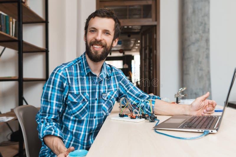 Glücklicher Programmierer, der an der Kamera nahe Laptop lächelt stockfotografie