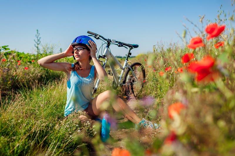 Glücklicher Radfahrer der jungen Frau, der ihren Sturzhelm nimmt, weg nachdem Fahrrad auf dem Sommergebiet gefahren worden ist lizenzfreies stockfoto