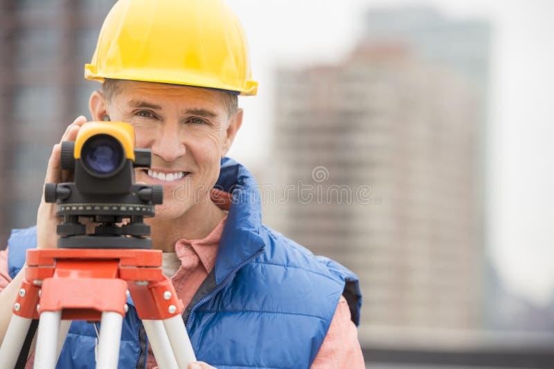 Glücklicher reifer Bauarbeiter With Theodolite stockfoto