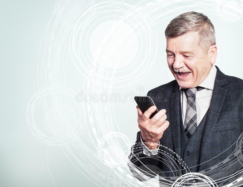 Glücklicher reifer Geschäftsmann, der einen Handy auf High-Techem Hintergrund verwendet lizenzfreie stockfotografie