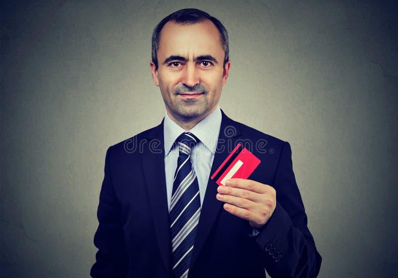 Glücklicher reifer Geschäftsmann, der neue Kreditkarte anbietet lizenzfreie stockfotos