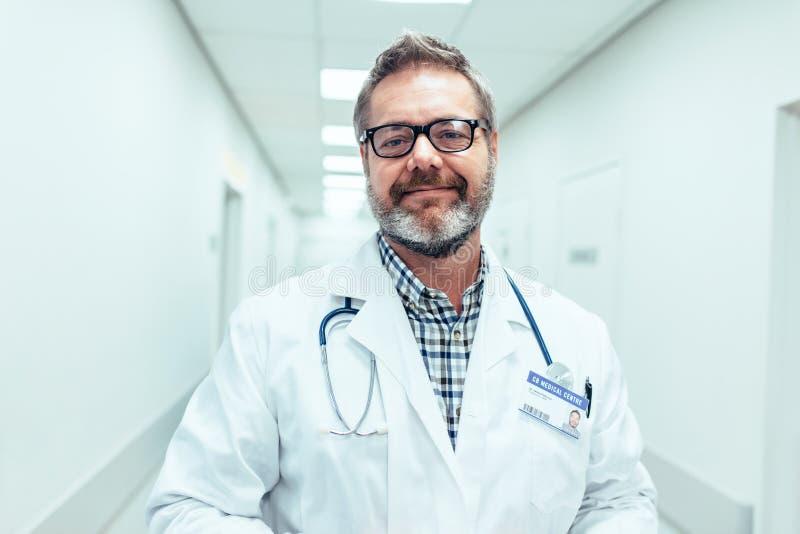 Glücklicher reifer männlicher Doktor, der im Krankenhauskorridor steht stockfoto