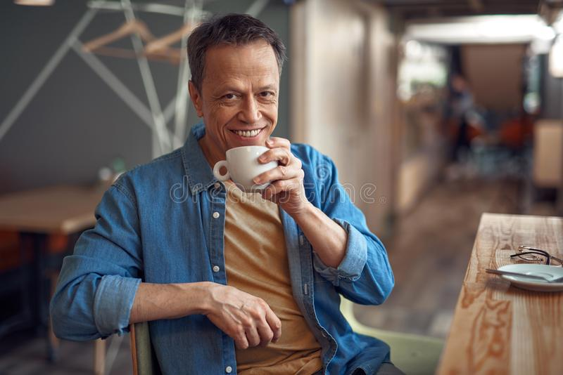 Glücklicher reifer Mann, der im Café mit Kaffee sitzt lizenzfreies stockfoto