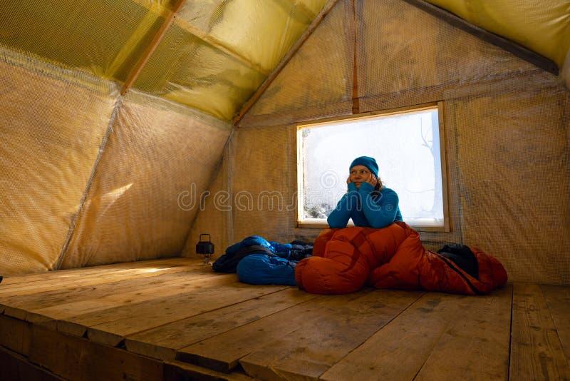 Glücklicher Reisender, Frau entspannt sich in der alten Gebirgshütte lizenzfreie stockfotografie