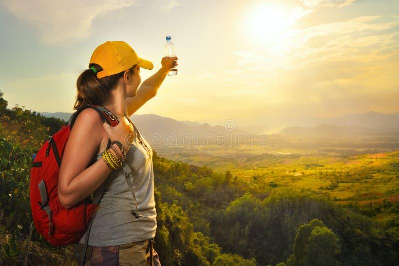 Glücklicher Reisender mit dem Wanderer, der Sonnenuntergangansicht mit angehoben genießt stockfotos