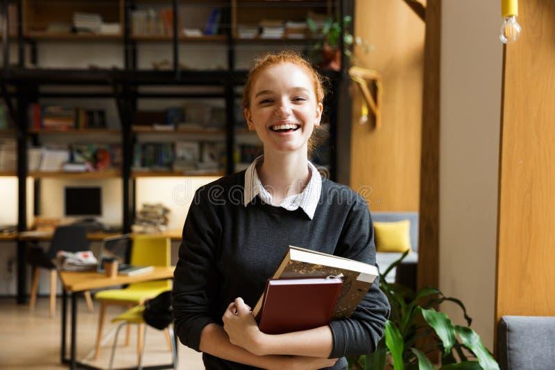 Glücklicher Rothaarigedamenstudent, der zuhause in den Bibliotheksbestandbüchern aufwirft lizenzfreies stockbild