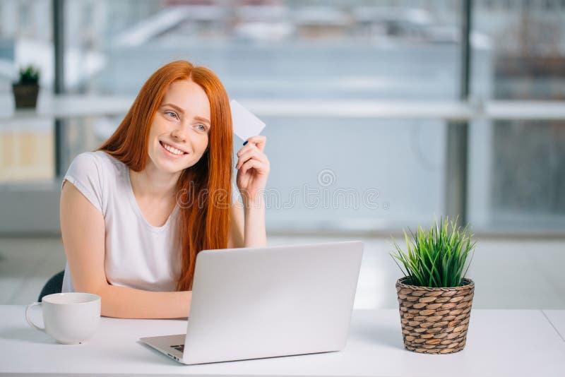 Glücklicher Rothaarigekäufer, der was entscheidet, auf der Linie zu kaufen hält ein Kreditkartesitzen stockfotografie