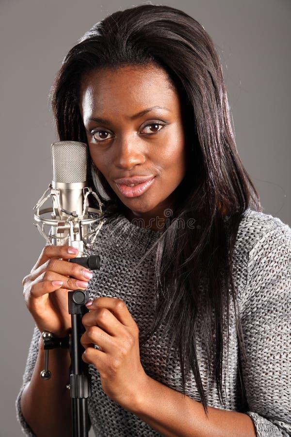 Glücklicher Sänger der schwarzen Frau des Portraits im Musikstudio lizenzfreies stockbild