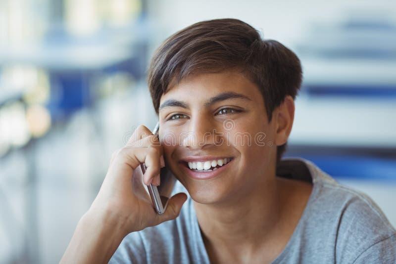Glücklicher Schüler, der am Handy im Klassenzimmer spricht lizenzfreies stockfoto