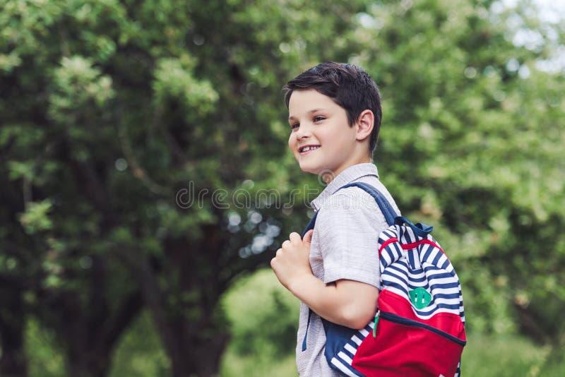 glücklicher Schüler mit dem Rucksack, der weg schaut lizenzfreie stockfotos