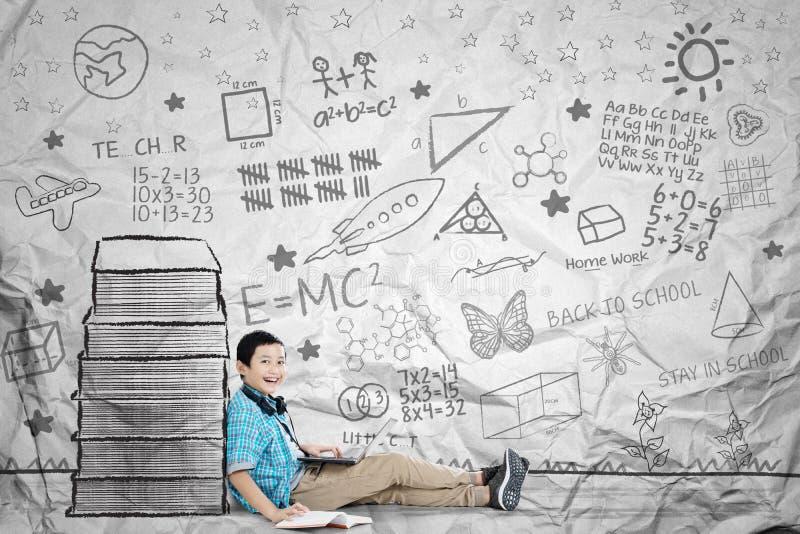Glücklicher Schüler tut schulische Arbeiten nahe Büchern lizenzfreies stockbild
