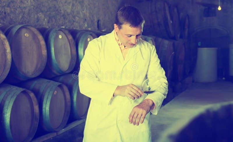 Glücklicher Schmecker, der mit Glas Wein aufwirft stockfoto