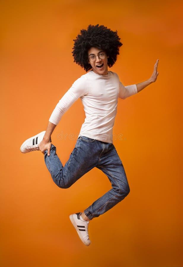 Glücklicher schwarzer Kerl, der auf orange Studiohintergrund springt lizenzfreies stockfoto