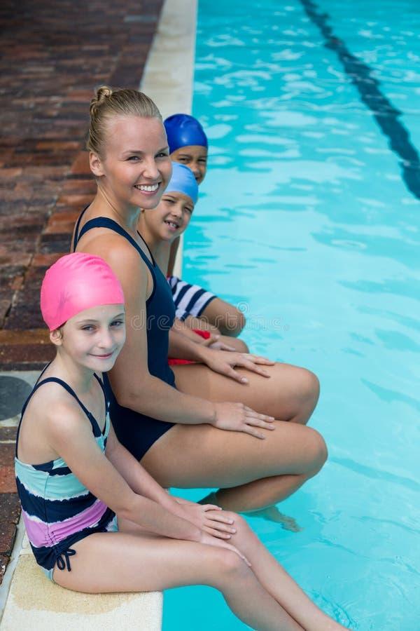 Glücklicher Schwimmenlehrer mit den Studenten, die am Poolside sitzen lizenzfreie stockbilder