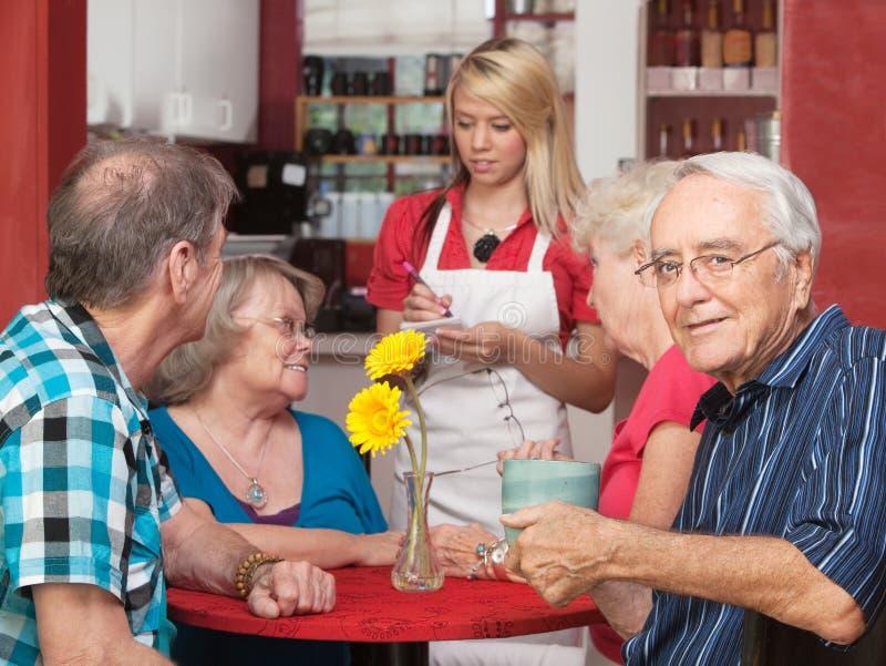 Glücklicher Senior mit Freunden im Café lizenzfreie stockfotografie