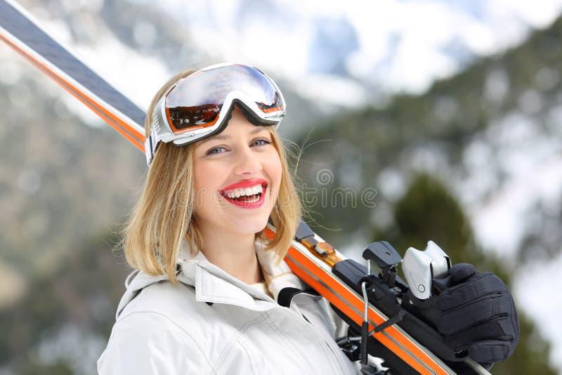 Glücklicher Skifahrer, der die Kamera hält Skis betrachtet stockfoto